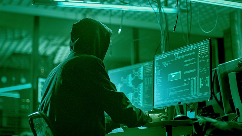 man in hood working at computer