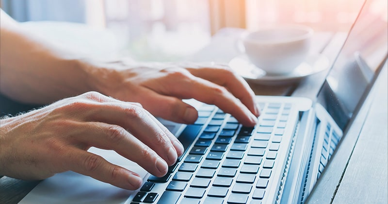 man typing with computer keyboard